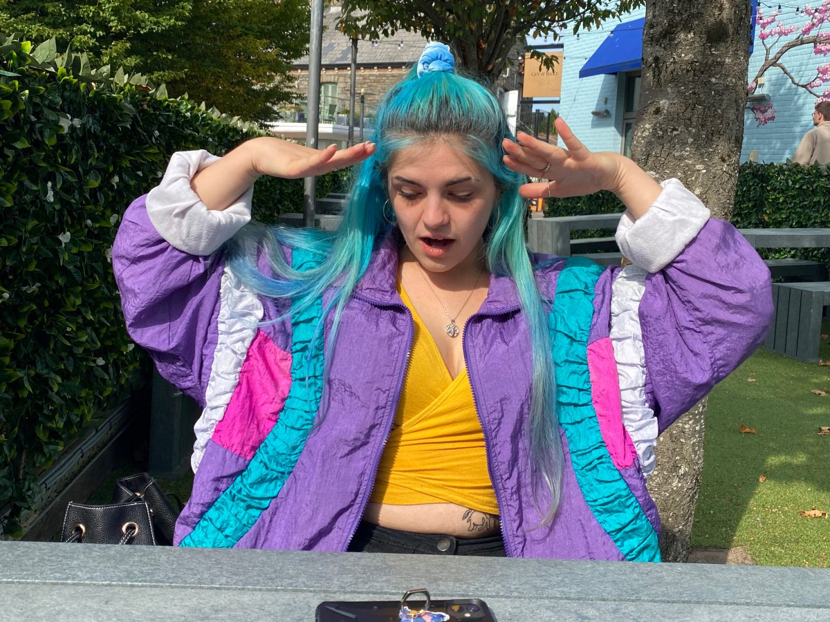 Maude sits outdoors wearing a brightly coloured windbreaker jacket. She has an exasperated expression and her hands beside her face.