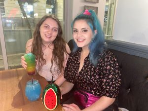 Maude and a friend sit inside a pub drinking alcohol