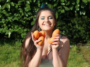 Maude smiles at the camera with her hands full of orange plastic eggs
